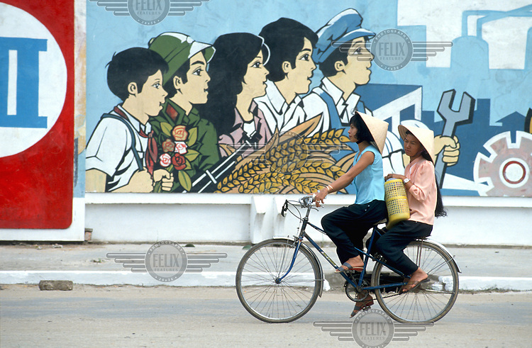 Vietnam, Mekong Delta..Women sharing a bicycle passing communist propaganda mural. .©Mark Henley