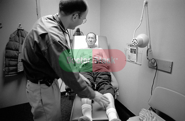 Male doctor examining legs of elderly male patient on examination table