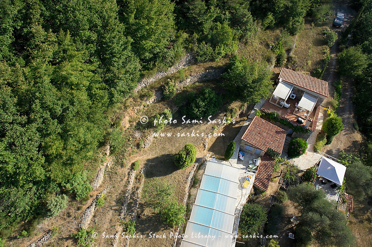 House with a covered swimming pool in mountains, aerial view, South of France