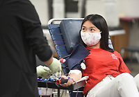 Phlebotomist Maddie Baker (from left) draws blood from Erica Vu, 17, Monday, April 26, 2021 at Rogers New Tech High School in Rogers. The Community Blood Center of the Ozarks held a student organized blood drive with the goal of collecting 49 units at the school. The school's student leadership promoted the event through videos and social media and helped check-in donors. They will have another drive on Wednesday at the Siloam Springs Regional Hospital and two others in Rogers at the Water Utilities on Friday and the First United Methodist Church on Saturday. Check out nwaonline.com/210427Daily/ for today's photo gallery. <br /> (NWA Democrat-Gazette/Charlie Kaijo)