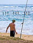A man stands by the ocean next to a fishing pole.
