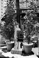 France. Ile-de-france Department. Paris. Restaurant's entrance. A Statue of Liberty with an economy menu. Trees in plant pots. Snow. Winter season. 25.02.05 © 2005 Didier Ruef