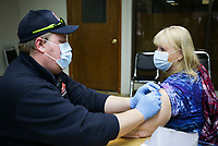 Paramedic Scott Larson (from left) administers a covid-19 vaccine to Peggy Furman of Bella Vista, Friday, February 12, 2021 at Riordan Hall in Bella Vista. Community paramedics from the Bella Vista Fire Department administered second doses of the covid-19 vaccine to people in the 1-B category. Check out nwaonline.com/210213Daily/ for today's photo gallery. <br /> (NWA Democrat-Gazette/Charlie Kaijo)