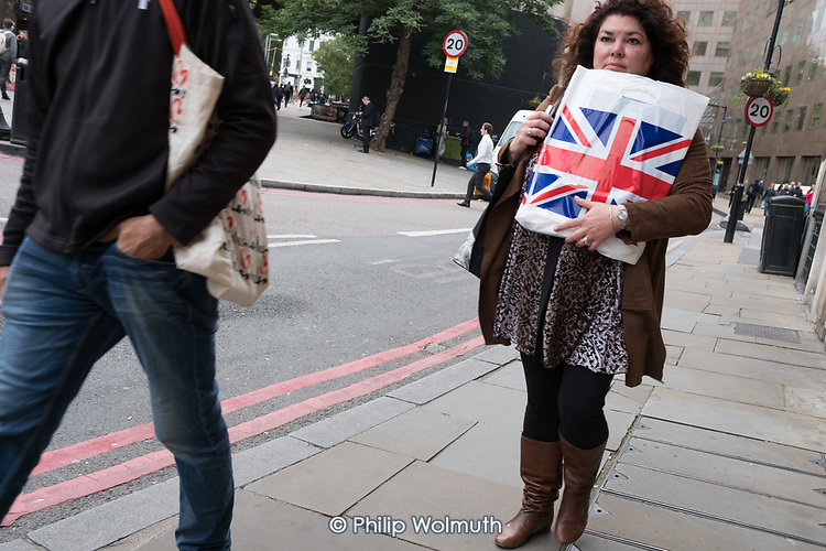 Woman with a Unon Jack shopping bag, London.