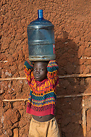 """A boy carries a heavy water jug from the local well at Kakira Sugar Estate Plantation in Jinja District, Uganda, Africa. There is no running water in any of the homes of this poor area where most people work on the affiliated sugar planation. It's often the children who are sent to the well to fetch the water in whatever containers they can find. The well at least affords them clean drinking water, whereas in many other areas locals are reliant on the often unclean rivers or lakes for drinking water. I was photographing for BRAC, a non-profit focused on micro-finance loan projects in developing countries. In this township they were helping children rise above their circumstances through scholarship programs to attend to school. """"The only hope we have,"""" one mother told me, """"is for our children to attend school and have a better life than we have."""""""