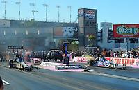 Oct. 30, 2011; Las Vegas, NV, USA: NHRA top fuel dragster driver Tony Schumacher (left) races alongside teammate Antron Brown during the Big O Tires Nationals at The Strip at Las Vegas Motor Speedway. Mandatory Credit: Mark J. Rebilas-