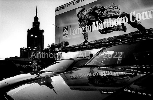 Warsaw, Poland.August 1997.The Marlboro man leaps a number of expensive cars heading in the direction of the massive old Soviet building in central Warsaw. It often appears as if the country suffers from the worst of the east and the west..