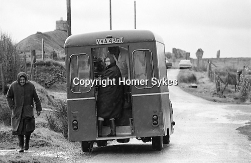 """Local women shopping at the weekly mobile shop Callanish.  Callanish Standing Stones in distance. Isle of Lewis and Harris,  Outer Hebrides, Highland and Islands Scotland 1974. On the side of the van its says """"M & A Cameron General Stores Roy Bridge"""" Morag lived until she was 105 yrs died in 2015 and her twin brother Alasdair lived until he was in his eighties. They were well know business family in the community."""