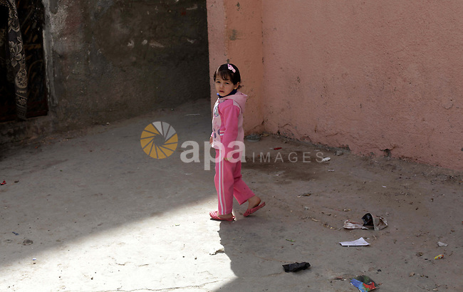 """A Palestinian girl walks in front of her home in al-Shatee refugees camp western Gaza city, on march 13, 203. Israel is trying to go through the UN to change the legal nature of Palestinian refugees and deny """"refugee"""" status from the Palestinians who were forced to leave their homeland in 1948, The Department of Refugees' Affairs in Hamas movement said. Photo by Ashraf Amra"""