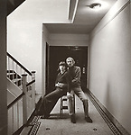Vintage black and white print scan. Sue Schaeffer and husband in NYC apartment hallway.. File #79-304-10.