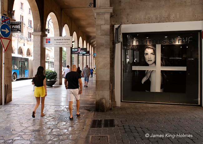 Shoppers in the cool arcades of the Avenguda Rei Jaume lll. This street is one of the principal retailing areas of Palma de Mallorca, Spain, with many fashion brands represented.