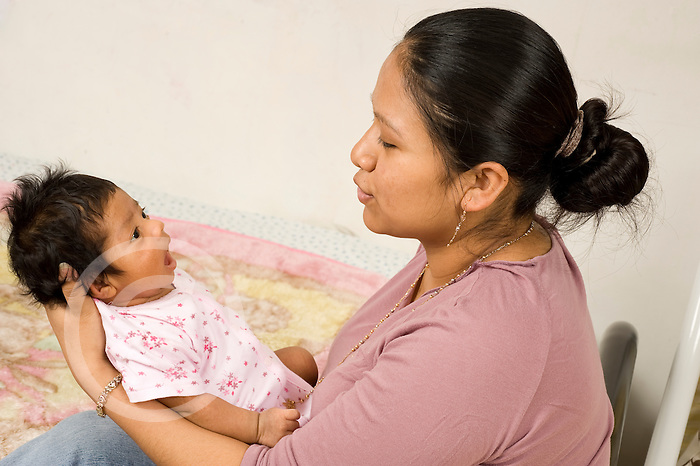 newborn baby girl one month old with mother held interaction horizontal Hispanic Mexican American