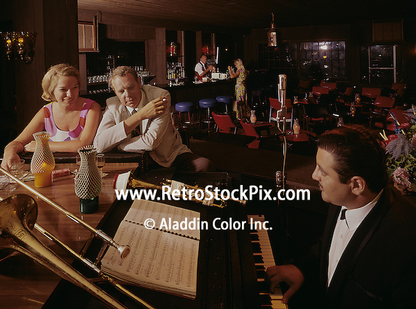 Couple enjoying the piano players music with bar counter in background at restaurant