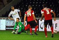Pictured L-R: Luke Moore of Swansea shoots the ball past goalkeeper Ben Alnwick to score a goal. Tuesday 28 August 2012<br /> Re: Capital One Cup game, Swansea City FC v Barnsley at the Liberty Stadium, south Wales.