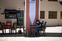 """BOGOTA - COLOMBIA, 05-09-2020: Un comensal espera durante el primer día del piloto de apertura de restaurantes y cafés al aire libre, denominado """"Bogotá a Cielo Abierto"""", en el Chorro de Quevedo en el centro de Bogotá que ahora tiene sus calles pintadas con formas geométricas en pintura neón y cuenta con mesas, distribuidas estratégicamente para mantener el distanciamiento físico al finalizar la cuarentena total en el territorio colombiano causada por la pandemia  del Coronavirus, COVID-19. / A dinner waits during the first day of the pilot for the opening of restaurants and outdoor cafes, called """"Bogotá a Cielo Abierto"""", in Chorro de Quevedo in the center of Bogotá, which now has its streets painted with geometric shapes in neon paint and has tables, strategically distributed to maintain physical distancing at the end of the total quarantine in the Colombian territory caused by the Coronavirus pandemic, COVID-19. Photo: VizzorImage / Johan Rugeles / Cont"""