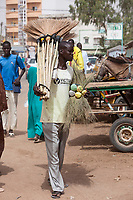 Senegal, Touba.  Broom Salesman in the Market.