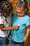 Preschool pretend play girl using stethoscope on another girl vertical