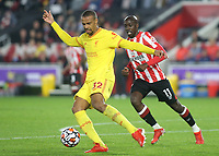 Joel Matip of Liverpool in possession as Brentford's Yoane Wissa looks on during Brentford vs Liverpool, Premier League Football at the Brentford Community Stadium on 25th September 2021