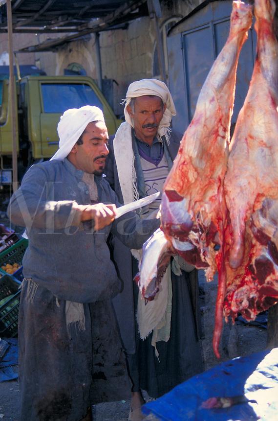 A streetmarket butcher in Yemen selects a cut of meat for a customer. Yemen.
