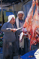 A streetmarket butcher in Yemen selects a cut of meat for a customer. Yemen.