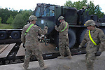 "Americans with the 15th Engineer Battalion unload a light equipment transporter from the railhead at the Drawsko Pomorskie Training Area in Poland on June 10, 2015.  NATO is engaged in a multilateral training exercise ""Saber Strike,"" the first time Poland has hosted such war games, involving the militaries of Canada, Denmark, Germany, Poland, and the United States."