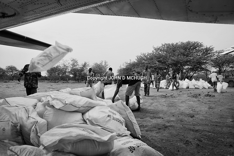 Humanitarian aid is hastly unloaded from a plane and into pickups at an undisclosed location in South Kordofan, 6 July 2011. On the 5 June, after almost 10 years of relative peace, Sudan's President Omar Al-Bashir sent his army, the Sudan Armed Forces (SAF), to attack on the people of the Nuba Mountains in South Kordofan, using MiG fighters to shoot at vehicles, and Antonov cargo planes, converted to use as heavy bombers. (John D McHugh)