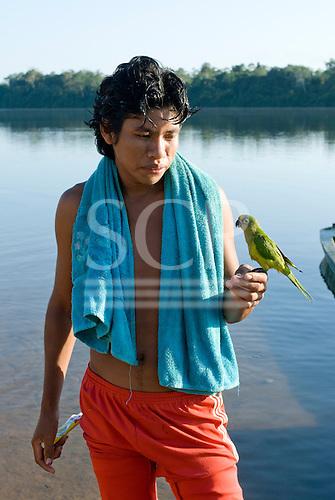 Pará State, Brazil. Iriri River. Aldeia Kararaô (Kayapó). Briti Kayapó with pet parrot.