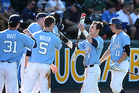 Brandon Riley (1) of the North Carolina Tar Heels greets his teammates Josh Hiatt (31), Brian Miller (5), and Cody Roberts (11) during a game against the UCLA Bruins at Jackie Robinson Stadium on February 20, 2016 in Los Angeles, California. UCLA defeated North Carolina, 6-5. (Larry Goren/Four Seam Images)