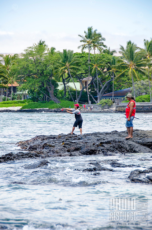 A local fisherman casts his line as another looks on at a beach in Puako, South Kohala, Hawai'i Island.