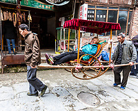 Longji, China. Village Men Carry Tourist in a Sedan Chair to Higher Portions of the Village.