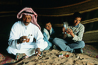 """Jordan. Wadi Rum.The Wadi Rum is a large, beautiful and deserted area where bedouins live under tents. Man dressed in traditionnal bedouin clothes - long white dress                      """" djellaba"""" and a turban on the head - seat on the sandy ground in the tent and drink tea. A teenage boy wears western clothes and plays with a plastic gun in his hands. The man works as a tourist guide.  © 2002 Didier Ruef"""