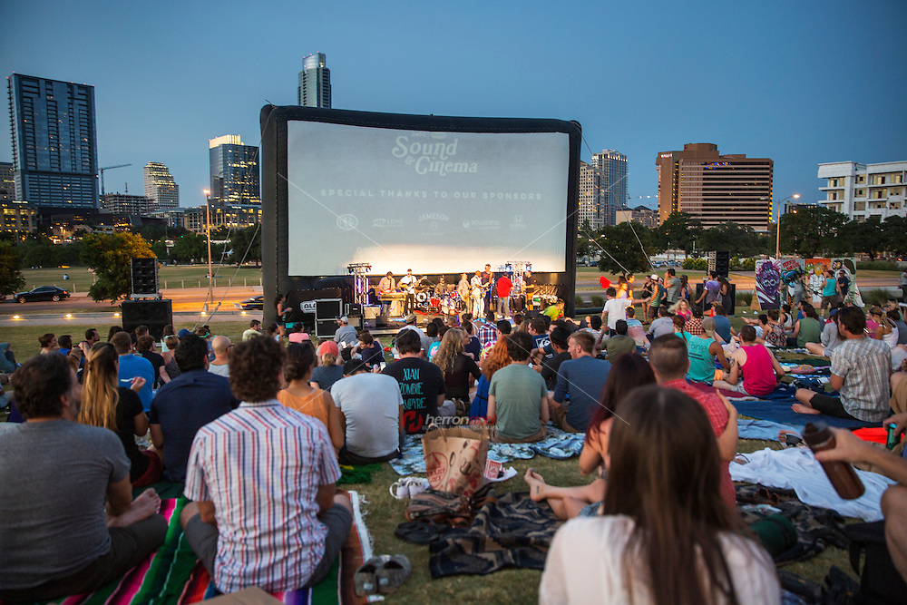 Music and movie fans gather at a free outdoors concert series and movie nights during summer. View from behind - Stock image.
