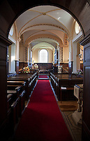 View from an arched entrance up the carpeted aisle of the family chapel