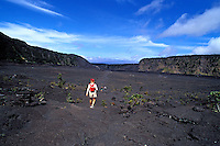 A lone hiker walks on the grey lava crust of Kilauea Iki Crater in Volcanoes National Park on the Big Island of Hawaii.