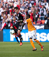 Kofi Sarkodie (8) of the Houston Dynamo tries to hold up Chris Pontius (13) of D.C. United during a Major League Soccer game at RFK Stadium in Washington, DC. D.C. United vs. Houston Dynamo, 2-1.