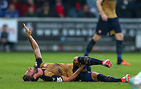 Olivier Giroud of Arsenal suffers an injury late in the first half but comes back on shortly after during the Barclays Premier League match between Swansea City and Arsenal played at The Liberty Stadium, Swansea on October 31st 2015
