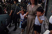 """Seoul, South Korea.June 27, 1987..A mother tries to protect her children from the overpowering tear gas that filled the streets of Seoul during a period of intense political rioting...After two decades of building an economic miracle, in the summer of 1987 tens of thousands of frustrated South Korean students took to the streets demanding democratic reform. """"People Power"""" Korean-style saw Koreans from all social spectrums join in the protests...With the Olympics to be held in South Korea in 1988, President Chun Doo Hwan decided on no political reforms and to choose the ruling party chairman, Roh Tae Woo, as his heir. The protests multiplied and after 3 weeks Chun conceded releasing oppositionist Kim Dae Jung from his 55th house arrest and shaking hands with opposition leader Kim Young Sam. Days later he endorsed presidential elections and an amnesty for nearly 3,000 political prisoners. It marked the first initiative of democratic reform in South Korea and the people had their victory."""