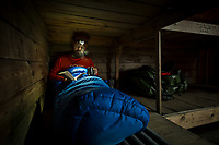 Hiker keeps warm inside his sleeping bag while reading a book, Iceland