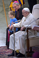 Pope Francis and Monsignor Georg Ganswein laughs as a boy who jumped from the audience onto the stage, interacts with a Swiss Guard during the weekly general audience on November 28, 2018 in Paul VI hall at the Vatican.