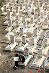 An Iraqi boy read Koran at a cemetery during the first day of a week-long curfew aiming to slow down the spread of the Coronavirus, in Baghdad, Iraq, on March 18, 2020. Photo by Hassouni al-Asadi