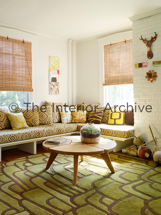 A custom built sofa is given a distinctly 1970's vibe with swirling brown and green patterned fabric.
