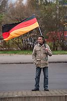 """Ca. 550 Neonazis, Hooligans, NPD-Mitglieder und Mitglieder der Neonazipartei """"Die Rechte"""", sowie eine sog. Buergerinitiative """"Gegen Asylmissbrauch den Mund aufmachen"""" protestierten am Samstag den 22. November 2014 gegen ein Fluechtlingsheim in Berlin Marzahn-Hellersdorf gegen eine geplante Unterkunft fuer Fluechtlinge.<br /> Dagegen protestieren bereits Stunden vor dem Aufmarsch ueber 3.500 Menschen an mehreren Punkten der Marschroute. Die Polizei lies sie zunaechst gewaehren.<br /> Bis zum Einbruch der Dunkelheit konnte der rechtsradikale Aufmarsch nur ca. 70 Meter Wegstrecke zurueck legen und wurde dann von der Polizei in einer chaotischen Aktion zum S-Bahnhof gebracht. Gegendemonstranten gelang es nach unverstaendlichen Polizeimanoevern bis auf wenige Meter an die Rechtsradikalen zu gelangen und es kam zu Auseinandersetzungen bei denen beide Seiten sich mit Flaschen, Steinen und Feuerwerkskoerpern beworfen.<br /> Im Bild: Ein Demonstrant mit Deutschlandfahne schaut sich nahe des Startplatzes der Rechtsradikalen um.<br /> 22.11.2014, Berlin<br /> Copyright: Christian-Ditsch.de<br /> [Inhaltsveraendernde Manipulation des Fotos nur nach ausdruecklicher Genehmigung des Fotografen. Vereinbarungen ueber Abtretung von Persoenlichkeitsrechten/Model Release der abgebildeten Person/Personen liegen nicht vor. NO MODEL RELEASE! Nur fuer Redaktionelle Zwecke. Don't publish without copyright Christian-Ditsch.de, Veroeffentlichung nur mit Fotografennennung, sowie gegen Honorar, MwSt. und Beleg. Konto: I N G - D i B a, IBAN DE58500105175400192269, BIC INGDDEFFXXX, Kontakt: post@christian-ditsch.de<br /> Bei der Bearbeitung der Dateiinformationen darf die Urheberkennzeichnung in den EXIF- und  IPTC-Daten nicht entfernt werden, diese sind in digitalen Medien nach §95c UrhG rechtlich geschuetzt. Der Urhebervermerk wird gemaess §13 UrhG verlangt.]"""