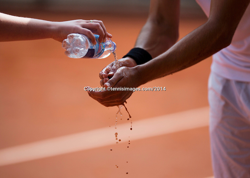 September 03, 2014,Netherlands, Alphen aan den Rijn, TEAN International, bellboy throws water over players hands after a fall on the clay court<br /> <br /> Photo: Tennisimages/Henk Koster