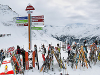 """Switzerland. Canton Valais. Ski tourists in Verbier at  """" La Chaux"""" ( 2260 meters ). Verbier is a village located in the municipality of Bagnes in the Val de Bagnes. Verbier is one of the largest holiday resort and ski areas in the Swiss Alps. Ski poles and skis in the snow. Rivella advertising. Indication signs. 3.01.2012 © 2012 Didier Ruef"""