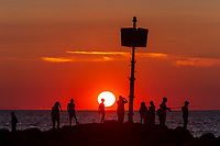 People stand on the jetty and watch the sunset over the Vineyard Sound at Menemsha Beach in Chilmark, Massachusetts on Martha's Vineyard.