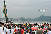 Indigenous people and others are gathering on Flamengo beach for the Human Banner event to protest about the construction of hydroelectric dams on Brazil's rivers while a jet aircraft flies over. The People's Summit at the United Nations Conference on Sustainable Development (Rio+20), Rio de Janeiro, Brazil, 19th June 2012. Photo © Sue Cunningham.