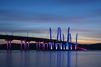 The Governor Mario M. Cuomo Bridge, illuminated in red, white, and blue in recognition of Columbus Day, spans the Hudson River just after sunset.