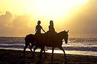 Two women horseback riding along the waters off sunset beach, Oahu