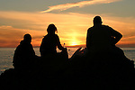 Friends gather to watch the sunset from Ballycastle Beach on the summer solstice, Ballycastle, County Antrim, Northern Ireland