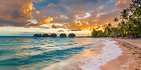 Dramatic sunset on famous Tikehau pink sand beach, coconut trees, and water bungalows in the lagoon, Tuamotus, French Polynesia, South Pacific Ocean